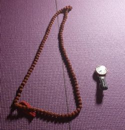 A picture of a Yoga mat with beads and a watch with devotion.